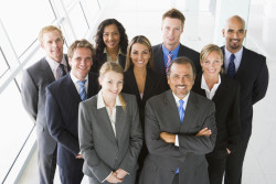 Group of co-workers standing in office space smiling (